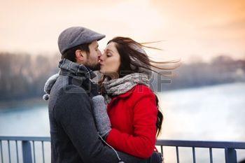 32450029-joven-pareja-bes-ndose-junto-al-r-o-en-el-invierno